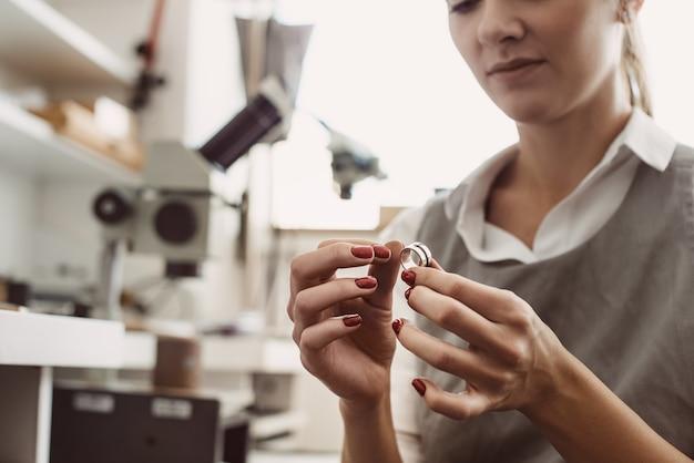 Нет предела совершенству. крупным планом женского ювелира, изучения серебряного кольца в мастерской. ювелир женщина осматривает ювелирные изделия.