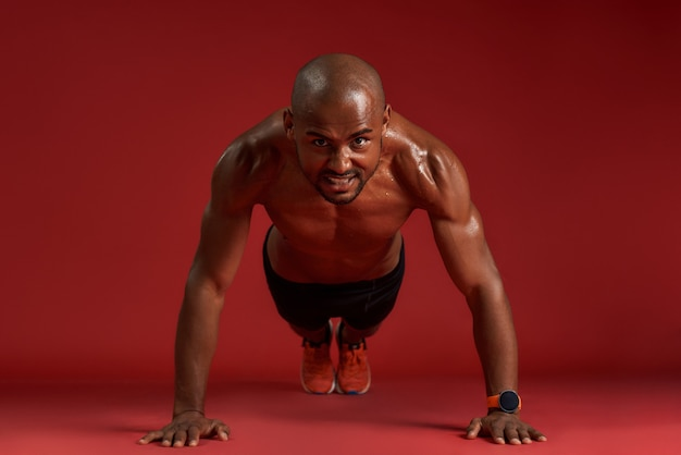 No limits full length of strong african man in sports clothing doing pushups isolated over