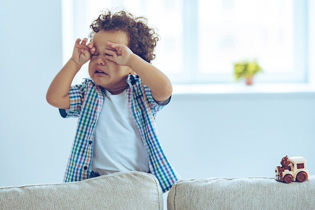 No! little african baby boy crying and rubbing his eyes while standing on the couch at home