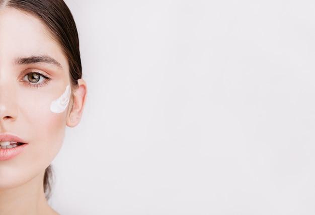 메이크업과 필터가 없습니다. 피부에 크림과 함께 건강한 녹색 눈을 가진 여자의 절반 얼굴의 사진.