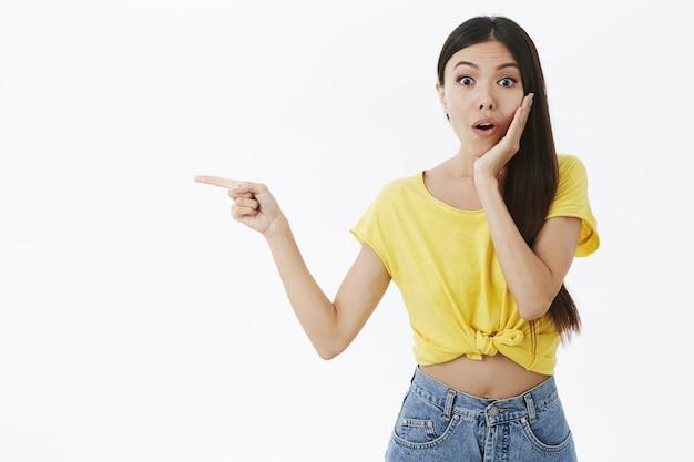 Nessun concetto di trucco, bellezza ed emozioni. femmina asiatica attraente incuriosita e sorpresa in maglietta gialla tagliata ansimante