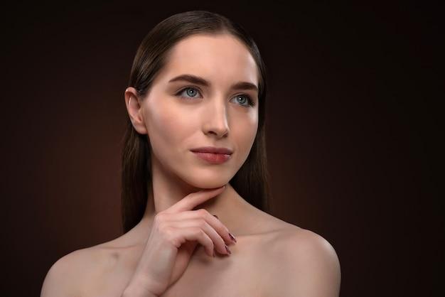 Без макияжа портрет красивой женщины с длинными волосами и открытыми плечами. очаровательная брюнетка