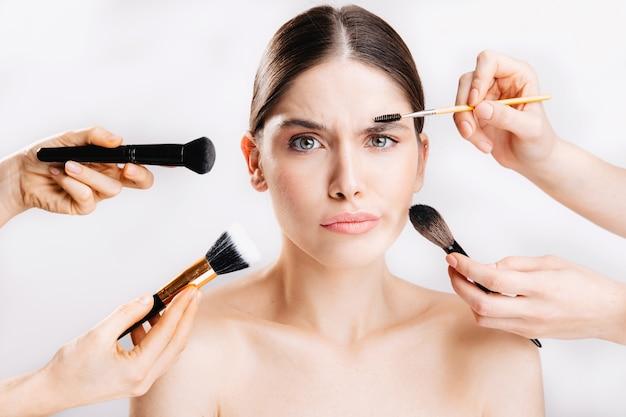 化粧なし。多くの手が彼女の化粧をしようとしている間、疑いのある女の子のショット。