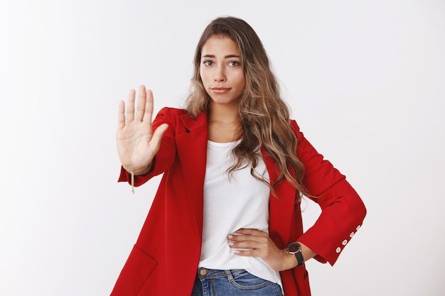 No means never. portrait disappointed unimpressed confident young 25s caucasian curly-haired woman wearing red jacket extending palm stop, refusal gesture, restraining, rejecting offer disliking it