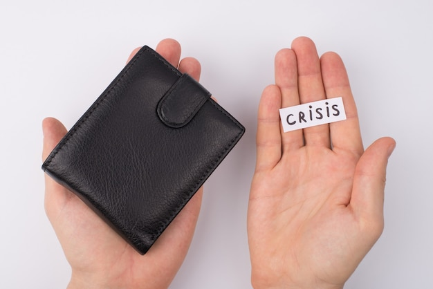 No money no job concept. pov cropped close up overhead top view photo of male hands showing closed wallet and word crisis lying on palm isolated over grey background
