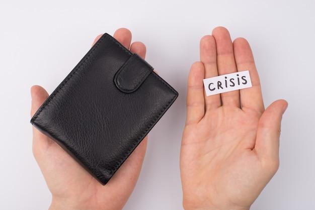 돈이 없는 직업 개념이 없습니다. pov cropped는 닫힌 지갑과 회색 배경 위에 격리된 손바닥에 누워 있는 단어 위기를 보여주는 남성 손의 오버헤드 상위 뷰 사진을 닫습니다.