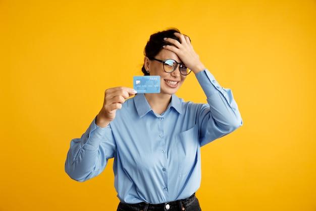 На карте нет денег. устали от продажи. дама в очках держит кредитную карту и положила руку ей на голову.