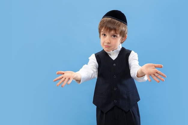 お金がない。青いスタジオの壁に隔離された若い正統派ユダヤ人の少年の肖像画。