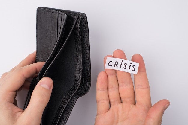No money and work concept. cropped close up overhead view photo of male hands holding empty open wallet and word crisis on palm isolated over grey background