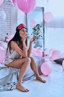Больше никаких развлечений. скучно молодая женщина в пижаме пьет шампанское, сидя на кровати