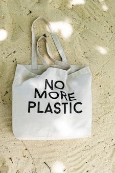 Эко сумка с концептуальной табличкой no more plastic на актуальном песчаном пляже, вид сверху