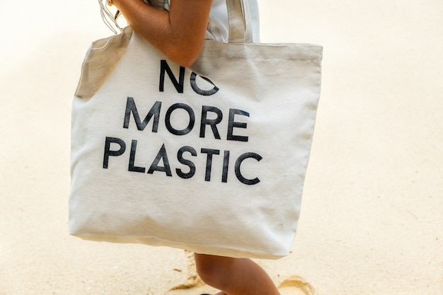 Эко-сумка с надписью no more plastic на плече молодой девушки