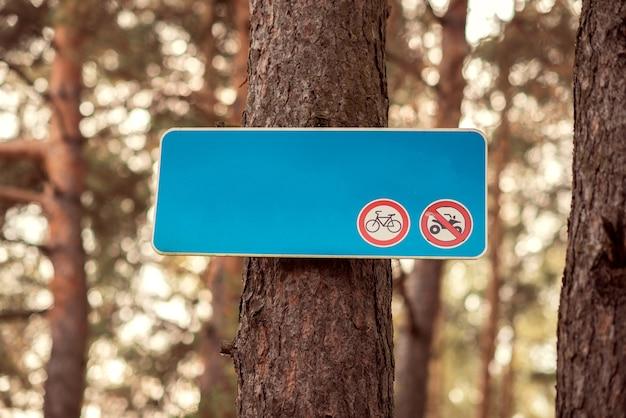 Знак запрета на использование мотоциклов на синей доске в лесу.