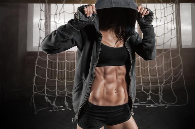 Безымянный портрет женщины с красивым прессом в толстовке в спортзале
