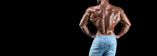 Без имени сексуальный мускулистый мужчина в джинсах позирует на черном фоне. вид сзади. бодибилдинг и фитнес-концепция. смешанная техника
