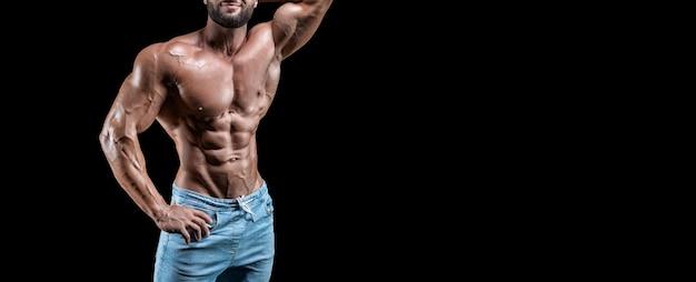 Без имени сексуальный мускулистый мужчина в джинсах позирует на черном фоне. бодибилдинг и фитнес-концепция. смешанная техника