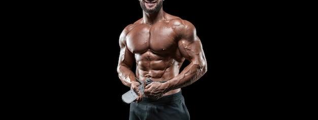 Без имени сексуальный мускулистый мужчина в джинсах позирует на черном фоне с поясом. бодибилдинг и фитнес-концепция. смешанная техника