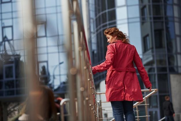 今日急ぐ必要はありません、休みです。暖かい赤いコートを着た大人のきれいな女性が彼女の週末の時間に街を歩いている