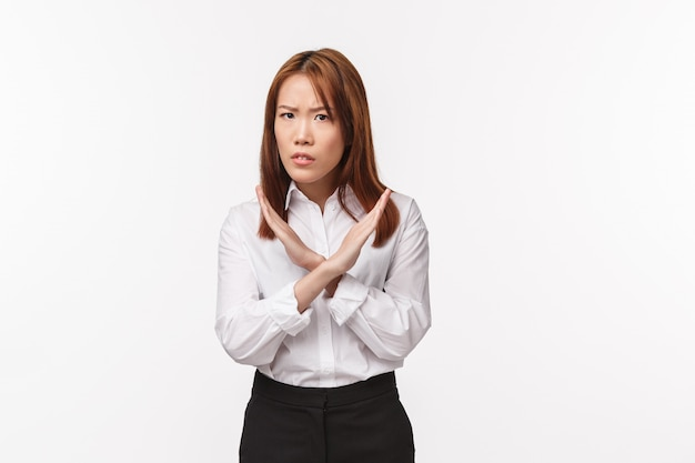 No, never. serious-looking angry and confident asian female entrepreneur showing cross gesture over chest, frowning and looking disapproval, prohibit action, forbid and disagree