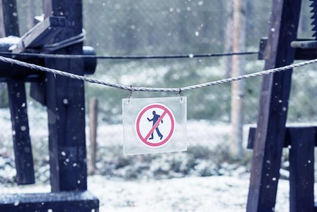 No pedestrian traffic sign on a snowy walking path