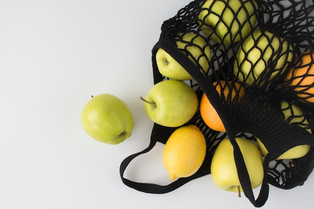 ビニール袋のコンセプトはありません。白いテーブルの上にさまざまな果物とメッシュショッピングの黒いバッグ。上面図。スペースをコピーします。