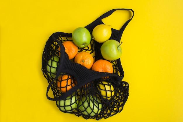 ビニール袋のコンセプトはありません。黄色の表面にさまざまな果物が入ったメッシュショッピングの黒いバッグ
