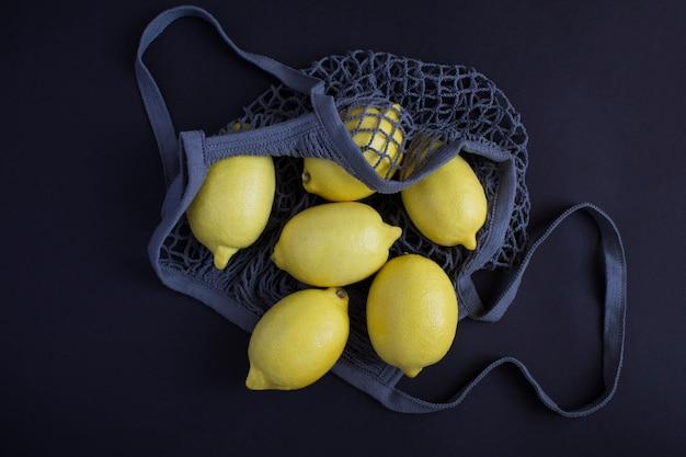 Нет концепции полиэтиленового пакета. сетка хозяйственная серая сумка с лимоном на черном фоне. вид сверху. крупный план.