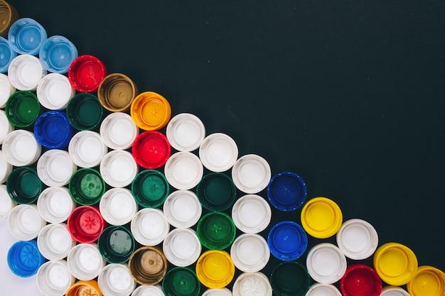 プラスチックの概念はありません。汚染問題のコンセプトです。斜めに配置された異なるプラスチック製の蓋の背景色。使い捨てプラスチックにはノーと言ってください。使い捨てプラスチックの概念を拒否