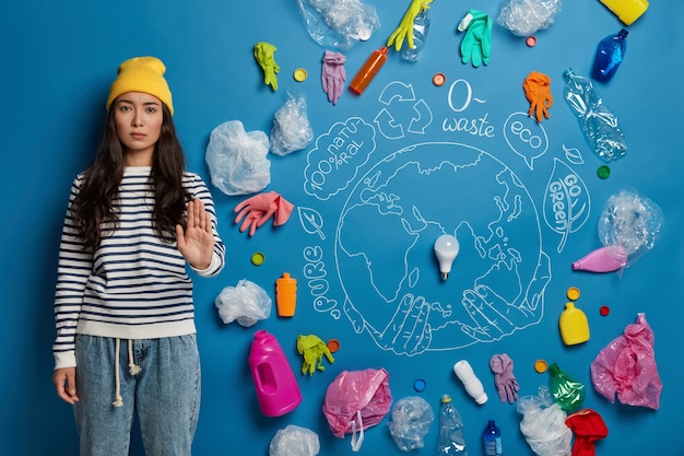 No plastic and environmental pollution. serious asian woman pulls palm forward, wears yellow hat, striped jumper and denim pants, asks not to pollute our planet