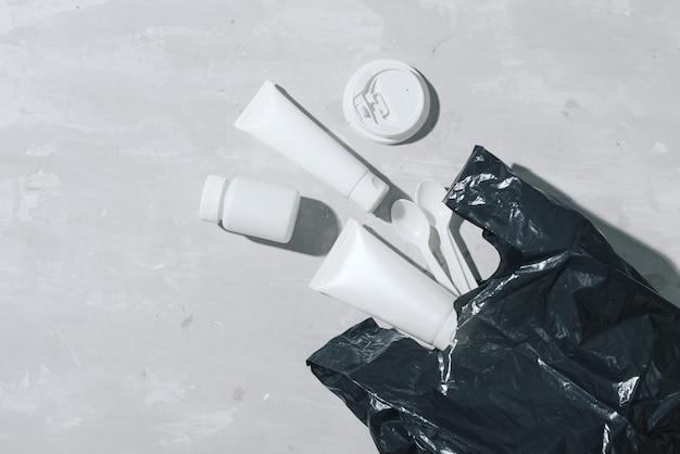 아니 플라스틱 재활용 개념 흰색 플라스틱 접시 접시 컵 숟가락 돌 배경. 공간을 복사하십시오. 평면도