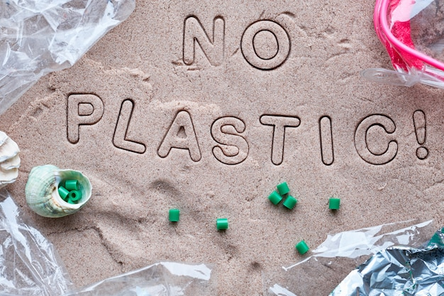 No plastic text on sand framed with plastic debris