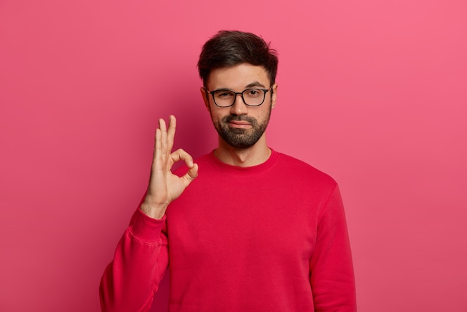 No problem concept. bearded man makes okay gesture, has everything under control, all fine gesture, wears spectacles and jumper, poses against pink wall, says i got this, guarantees something