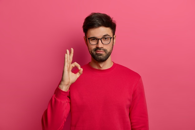 Концепция без проблем. бородатый мужчина делает нормальный жест, все держит под контролем, все хорошо жестикулирует, носит очки и джемпер, позирует у розовой стены, говорит, что я понял, что-то гарантирует