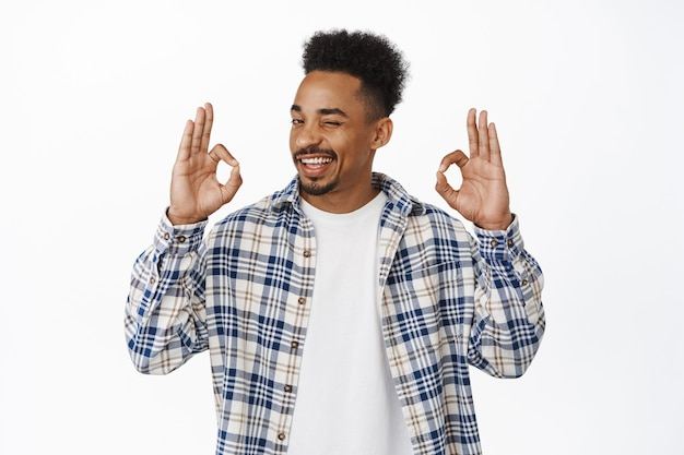 No problem. confident smiling african american guy assure all under control, winking and showing okay ok gesture, approve smth good, praise, being assertive in his choice on white.