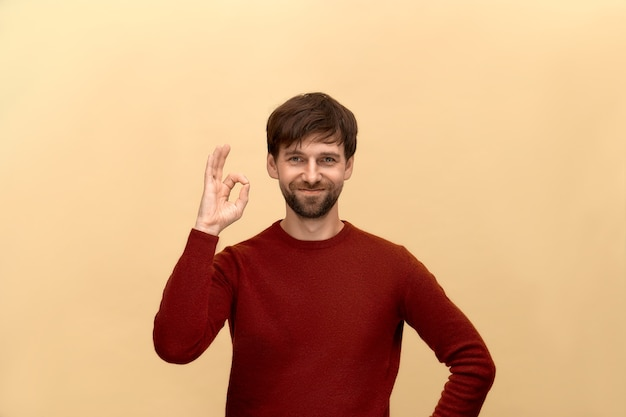Без проблем. фотография молодого человека с бородой в свитере, показывает хорошо знаком, улыбается, позирует у бежевой стены.