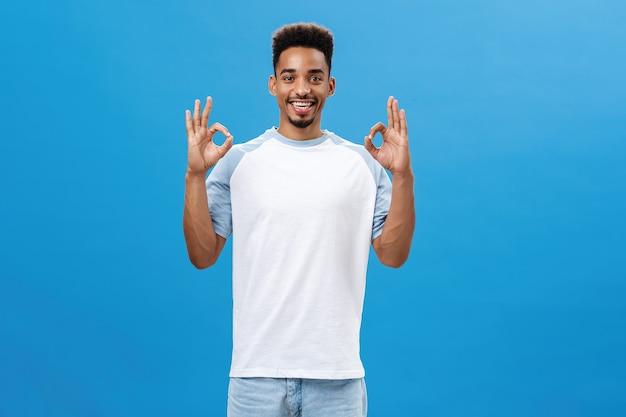 Без проблем. портрет радостного оптимистичного темнокожего парня с классной стрижкой в повседневной футболке показывает нормальный жест, которому нравится отличная идея улыбающегося друга, радостно позирующего на синем фоне
