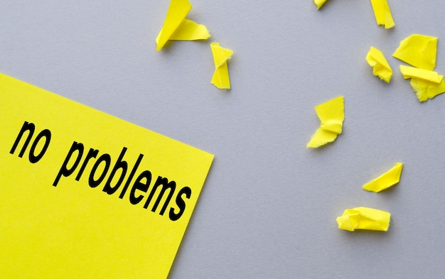 No problem a word written on yellow paper, next to torn shreds on a gray table, the concept of success.