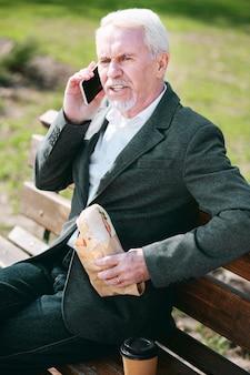 休みなしで。電話で話し、サンドイッチを消費する経験豊富な成熟したビジネスマンの上面図