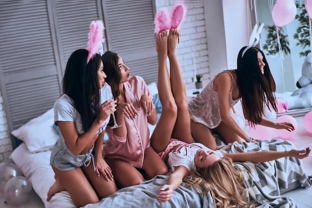何でもあり。ガールフレンドの足にバニーの耳をつけようとし、ベッドに座って笑っている遊び心のある若い女性