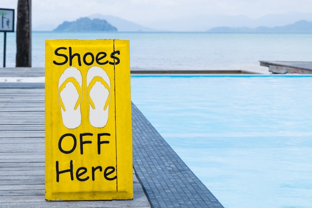 No shoes sign by the swimming pool on the wooden floor in yellow color