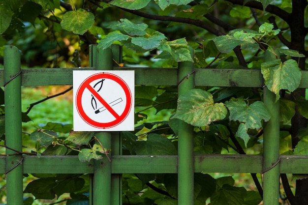 Знак не курить на заборе парка