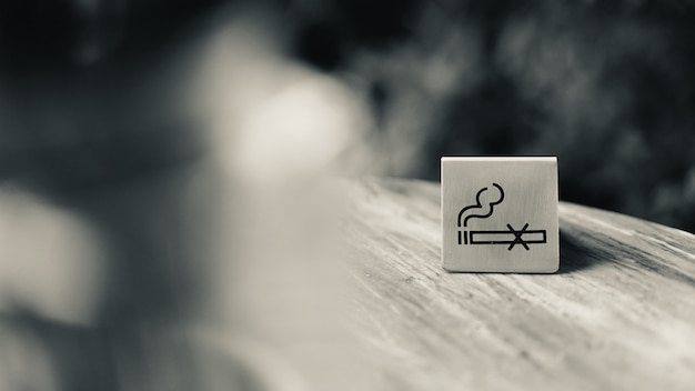No smoking sign plate on table in restaurant, black and white tone