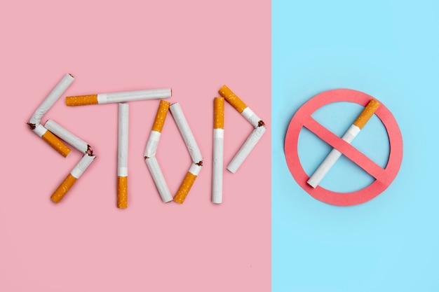 禁煙の標識。色付きの背景に壊れたタバコを使用して綴られた単語停止。