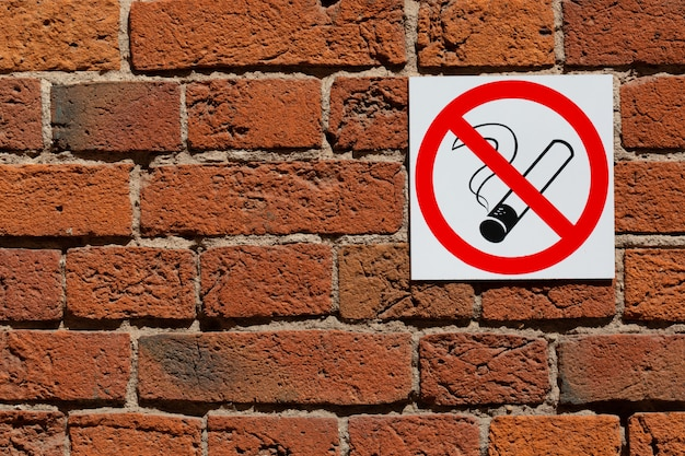 No smoking sign with cigarette symbol on red brick wall.