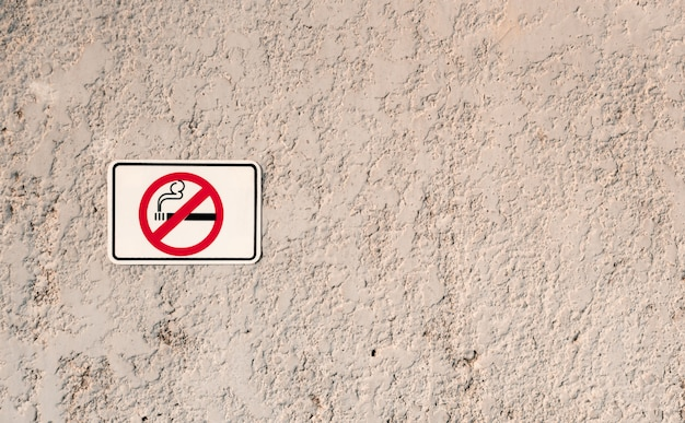 No smoking white sign with cigarette symbol on grunge stone texture wall,