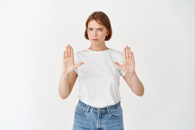 No stop right there. serious woman raising hands for block, frowning disappointed, rejecting bad offer, express negative opinion and decline, standing on white wall