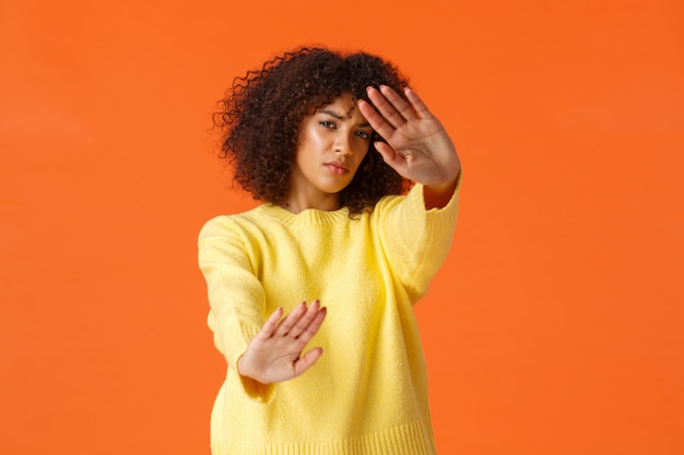 No stop, turn-off lights. displeased grumpy cute african-american woman with afro haircut cover face from spotlight, defending from glimmering light, standing orange  reluctant