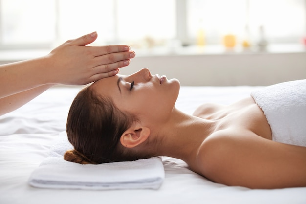 No stress. beautiful young woman lying on back while massage therapist touching her forehead with hands