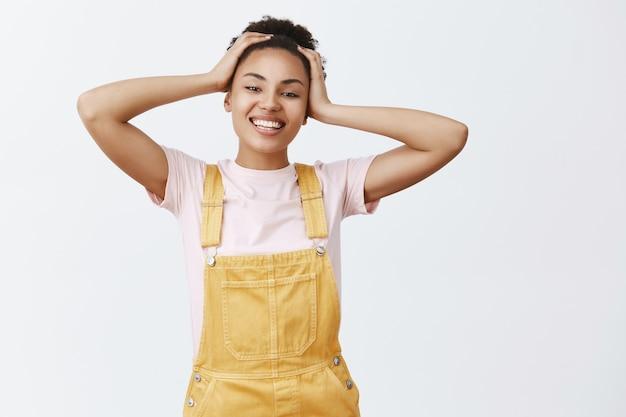 ストレスなく、リラックスする時間。黄色のスタイリッシュなオーバーオールでのんきな格好良い幸せなアフリカ系アメリカ人の女の子の肖像画、髪に触れ、広く笑って、素晴らしい昼寝の後に素晴らしい気分になっています