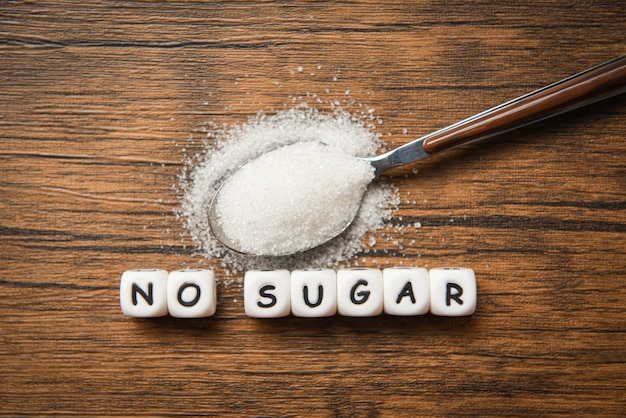 No sugar text blocks with white sugar on spoon wooden - suggesting dieting and eat less sugar for health concept